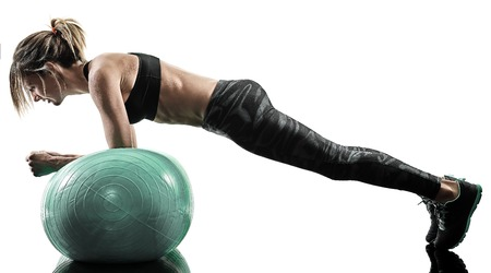Foto de one caucasian woman exercising pilates fitness swiss ball exercises isolated  silhouette on white background - Imagen libre de derechos