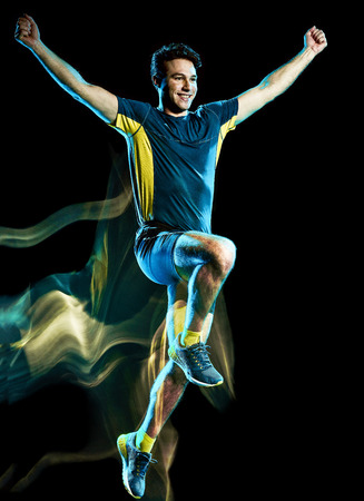 Foto de one caucasian runner running jogger jogging man light painting speed effect  isolated on black background - Imagen libre de derechos