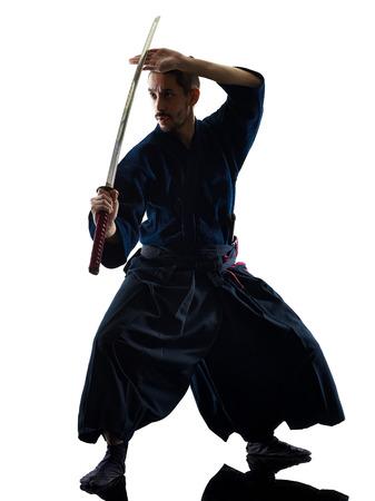 Photo pour one caucasian man practicing  laido  Katori Shinto ryu isolated shadow silhouette white background - image libre de droit
