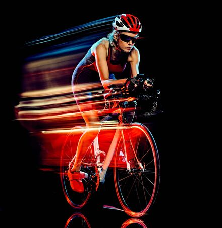 Photo for one caucasian woman triathlon triathlete cyclist cycling studio shot isolated on black background with light painting effect - Royalty Free Image