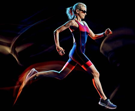 Photo pour one caucasian woman triathlon triathlete runner running joogger jogging studio shot isolated on black background with light painting effect - image libre de droit