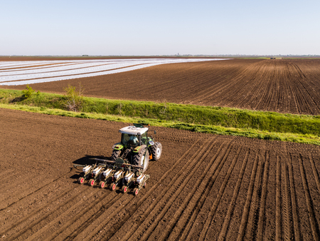 Aerial shot of a farmer seeding, sowing crops at field. Sowing is the process of planting seeds in the ground as part of the early spring time agricultural activities.