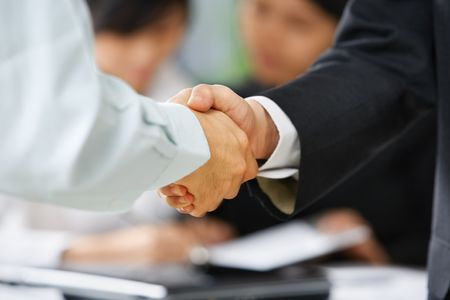 Handshake between employee and boss to ilustrate he is being accepted in the team