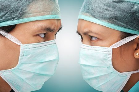Serious looking between two medical worker, close up to face