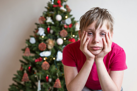 Boy sits near a Christmas tree his head in his hands