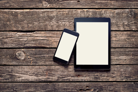 Black Apple devices - Iphone 6 plus and Ipad Air on old wood desktop. Clipping paths included.
