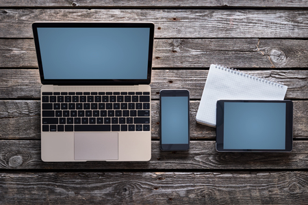 Photo pour Responsive mock-up of laptop, digital tablet and smartphone, top view on a desktop. Clipping paths for all screens are included. - image libre de droit