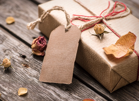 Gift tag with gift box on a vintage wooden background. Close-up