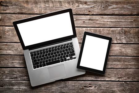 Foto de Open laptop with digital tablet. With isolated screen on old wooden desk. - Imagen libre de derechos