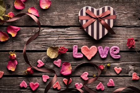 Photo pour Word Love with Heart shaped Valentines Day gift box on old vintage wooden plates. Sweet holiday background with rose petals, small hearts, curved ribbon. - image libre de droit