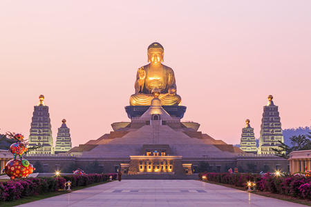 Kaohsiung, Taiwan - December 15, 2014: Sunset at Fo Guang Shan, the biggest buddist temple of Kaohsiung in Taiwan, with a buddhist monk walking by.