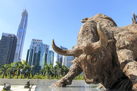 Shenzhen, China - August 19,2015: Stock market building in Shenzhen, one of the three stock markets in China, with the copper bull statue on foreground. The others two Stock Markets of China are in Hong Kong and Shanghai.
