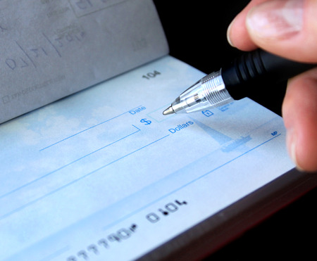 Photo pour financial concept - writing a check. the account numbers on the check are not real. - image libre de droit