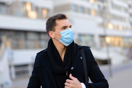 Photo pour Portrait of young handsome businessman with face mask in quarantine of flu. Photo in caffee with laptop, mobile phone. Coronavirus pandemic. - image libre de droit