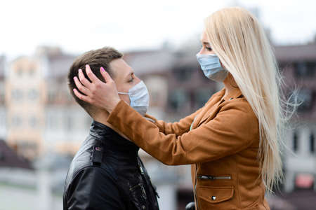 Photo pour Couple in protective masks have a walk outdoors in the city near business building at quarantine time. Conception of coronavirus pandemic. - image libre de droit
