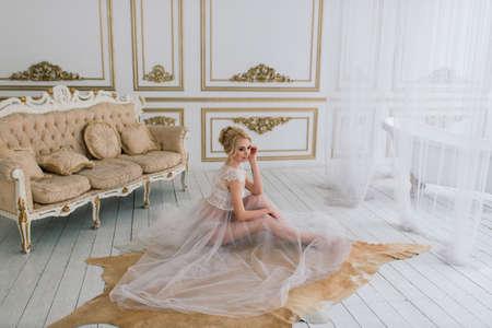 Photo pour Morning of a beautiful young bride in a boudoir dress. Studio, interior. - image libre de droit