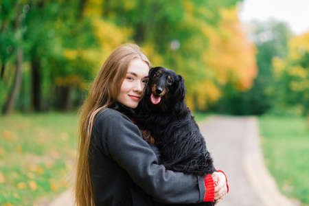 Photo pour Young attractive woman holding her dachshund dog in her arms outdoors in sunrise in park at autumn time - image libre de droit