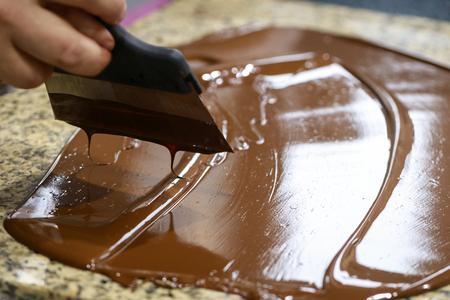 Foto de Chocolatier is stirring the tempered liquid chocolate - Imagen libre de derechos
