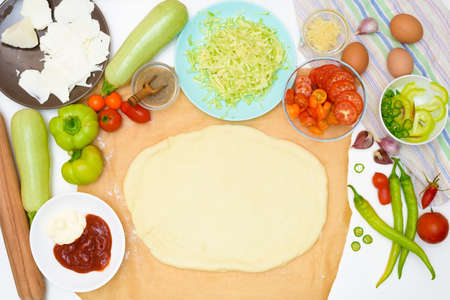 Photo for step by step recipe for cooking homemade vegan pizza with zucchini, tomatoes, peppers, mozzarella. hands of a woman preparing a pizza from the top view. light background. - Royalty Free Image
