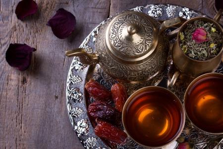 Photo pour Traditional arabic tea set and dried dates. Old wooden background - image libre de droit