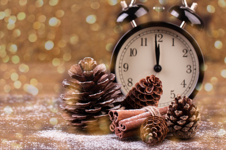 Photo pour New year decoration. New year clock and cones covered with snow. Selective focus. De-focused lights as background. - image libre de droit
