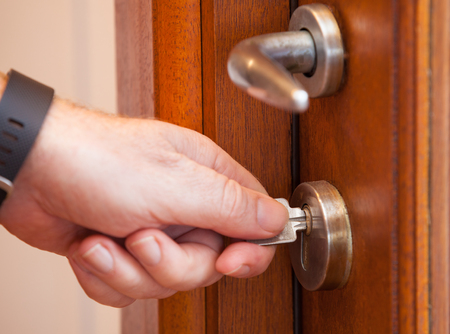 Photo pour Looking the door with a key. Protect your house by locking the door. Use the key to secure your home - image libre de droit