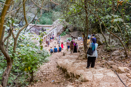 Unidentified people going down to stone stairs towards cave of Chasm of Heaven in Silifke district.Virgin Mary Church built by St. Paulus is in the background.Mersin Turkey.29 August 2017.