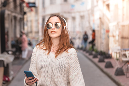 Photo pour Beautiful attractive young trendy girl in jumper and jeans with headphones smartphone and sunglasses listen music while walking in crowd - image libre de droit