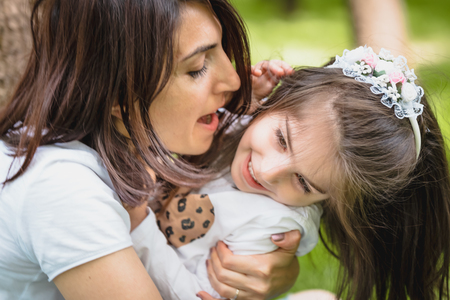 Photo pour Young mom hugs and has fun with her daughter while embracing.Happy mother hugging her daughter with love and natural emotion. - image libre de droit