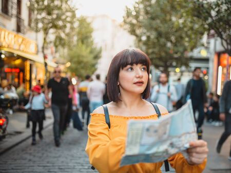 Photo pour Beautiful young girl in fashionable clothes with map walks around city and looks around.Traveler Concept image - image libre de droit