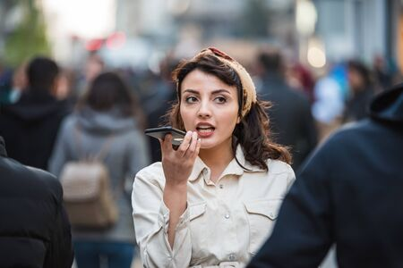 Photo pour Beautiful young girl in fashionable clothe holds and speaks activate virtual digital voice assistant on smartphone while walking in crowded people at busy street.Lifestyle technology concept. - image libre de droit
