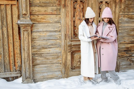 Two beautiful girls wearing warm winter clothes reading magazine outdoors.