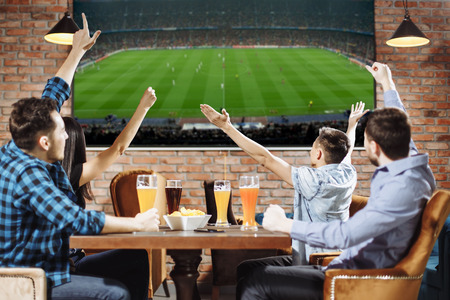 Photo pour Victory! Group of young beautiful friends watching TV and cheering for their team while resting in pub. - image libre de droit