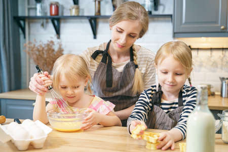 Photo pour Happy family young mother and two little daughters making dough for pancakes or cookies together in the kitchen. - image libre de droit