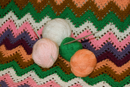 The balls of yarn for knitting, crochet and knitting needles on the associated colored canvas