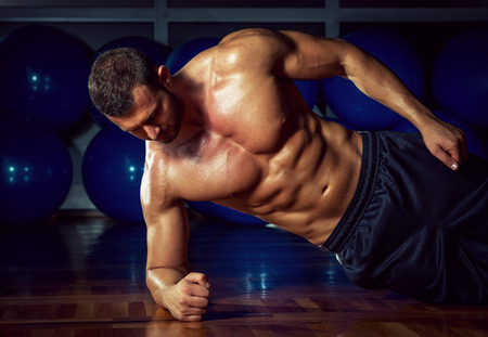 Foto de Man doing side plank exercise in gym - Imagen libre de derechos