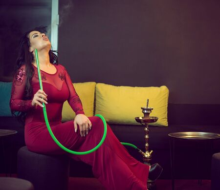 Young attractive girl in elegant dress smoking narghile hookah in bar
