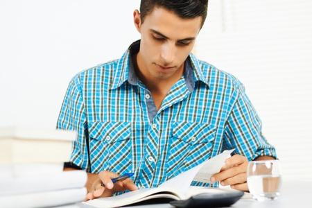 Photo pour Young man reading and taking notes. - image libre de droit