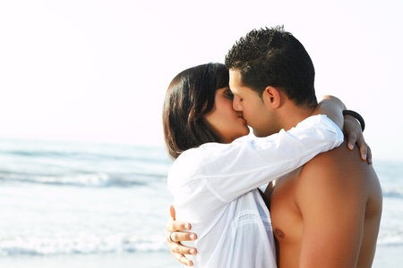 Photo for adorable close up  portrait of a loving couple  kissing and embracing each other on the edge of the beach - Royalty Free Image