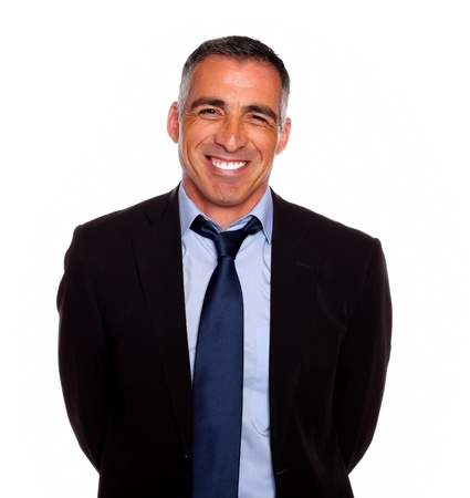 Portrait of a friendly hispanic businessman on black suit smiling with the arms on the back against white background