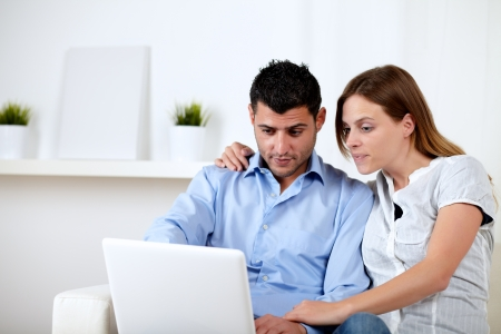Portrait of a friendly interested couple browsing on laptop at home indoor