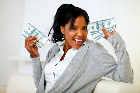 Portrait of an afro-american girl holding plenty of cash money while is looking to you