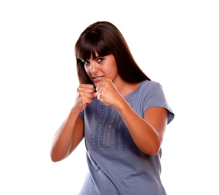 Angry latin young female with clenched fists looking at you on isolated background
