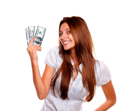 Portrait of a happy young woman holding up cash money while is looking at you on isolated backgroundの写真素材