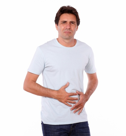Portrait of an attractive male with pain in stomach while standing on isolated background