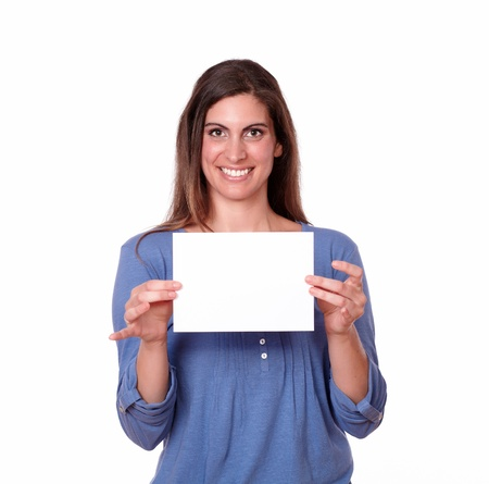 A portrait of a gorgeous hispanic young woman holding a white card while smiling and looking at you on isolated background - copyspace