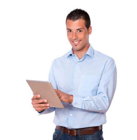 Portrait of a latin man on blue shirt working with his tablet pc while standing and smiling at you on isolated studio