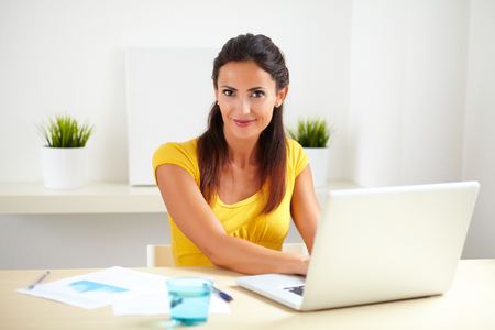 Pretty female working as a receptionist in a company while using her laptop