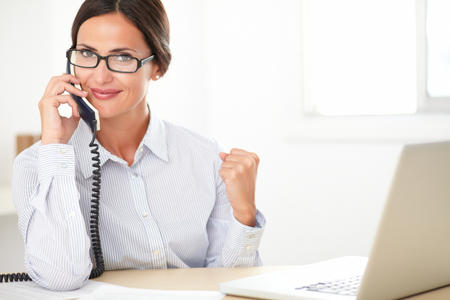 Pretty company secretary with glasses cheerfully conversing on the phone while using the computer in the office