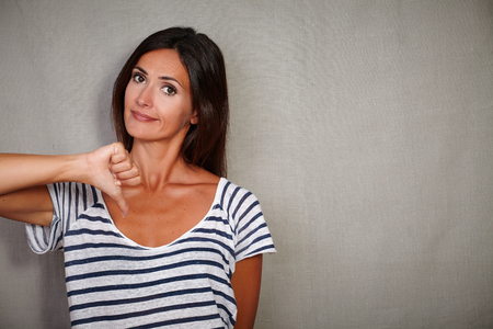 Young female in blue blouse looking at camera with finger down - copy space